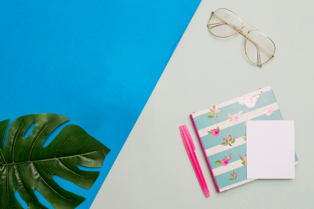 Notepad with glasses and leaf Free Photo