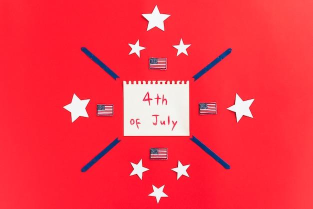 Blocco note con iscrizione 4 luglio e design con stelle su superficie rossa Foto Gratuite