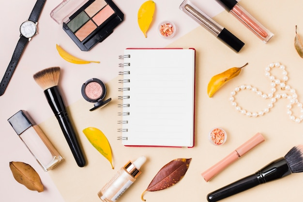 Notepad with makeup cosmetics on light desk Free Photo