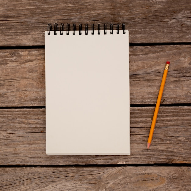 Notepad with pencil on wood board background Free Photo