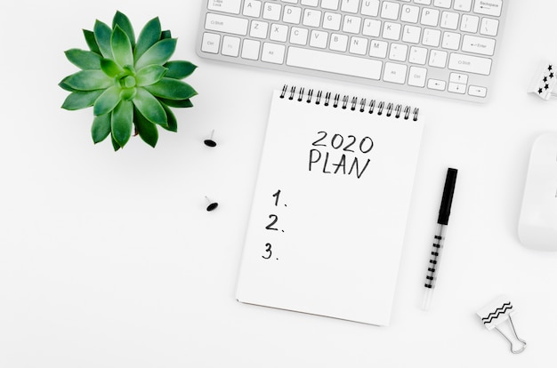 Notepad with stationery items and plant top view Free Photo