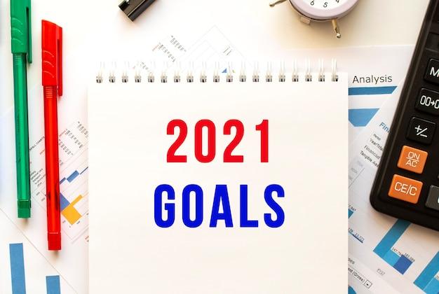 カラー財務チャートに2021goalsというテキストが記載されたメモ帳。ペン、オフィステーブルの電卓。 Premium写真