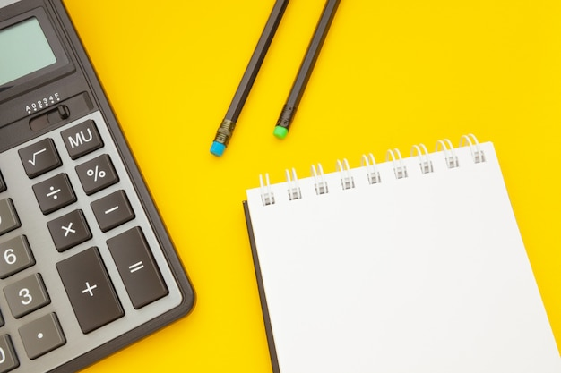 Notepad with two pencils and a calculator on yellow Premium Photo