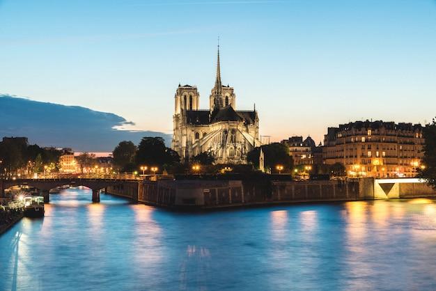 Notre dame de paris cathedral with seine river at night in paris, france. Premium Photo