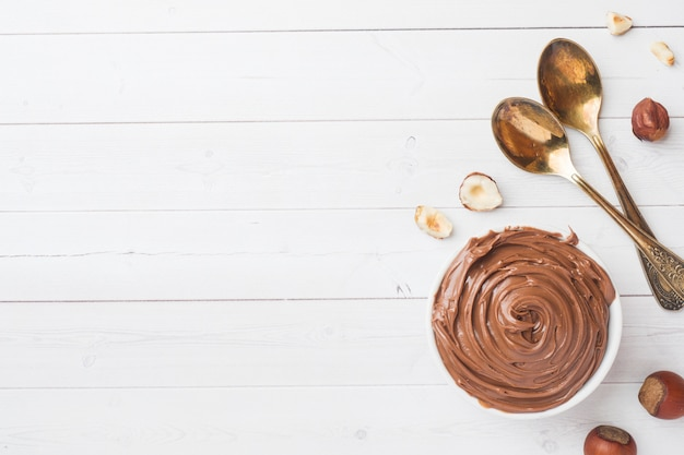 Nougat nut chocolate in a plate on a white background with hazelnut nuts. Premium Photo