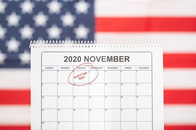 3 ноября 2020 года концепция дня выборов. настольный календарь с 3 ноября, отмеченным красным, и флагом сша на заднем плане Premium Фотографии