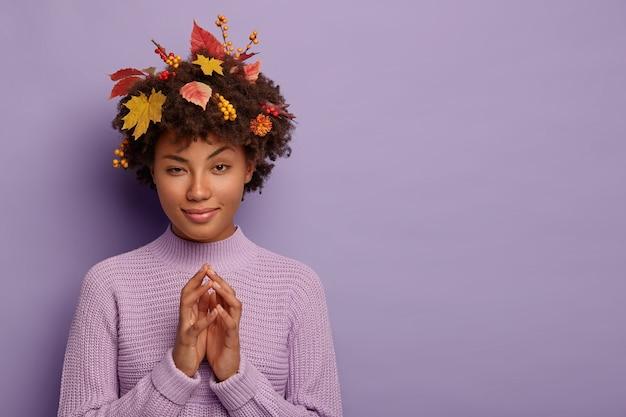 Donna riccia intrigata si strofina le palme, ha uno sguardo curioso, alza le sopracciglia, indossa un maglione lavorato a maglia, foglie gialle cadute dagli alberi, isolato su un muro viola Foto Gratuite