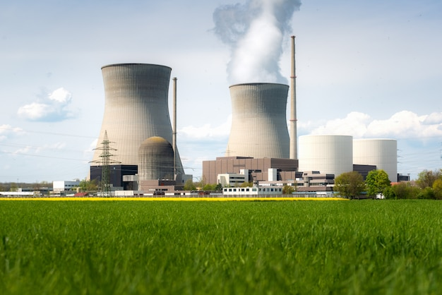 Nuclear power plant with yellow field and big blue clouds. Premium Photo