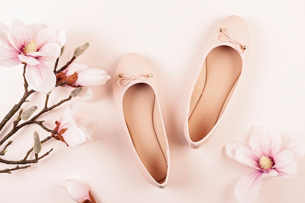 Nude colored ballerina shoes and magnolia flowers. Premium Photo