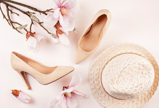 Nude colored high heels shoes and magnolia flowers Premium Photo