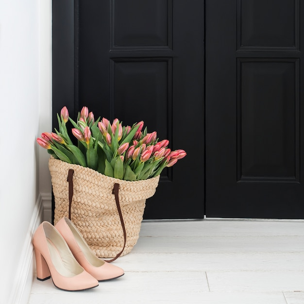 Nude shoes and straw bag with bunch of fresh pink tulips on floor near black door Premium Photo
