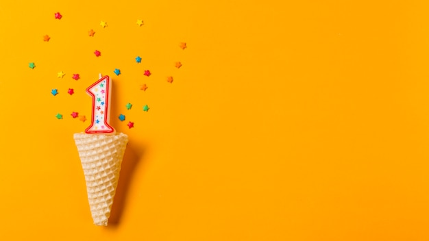Number 1 candle with colorful star sprinkles over the waffle cone on an orange backdrop Free Photo