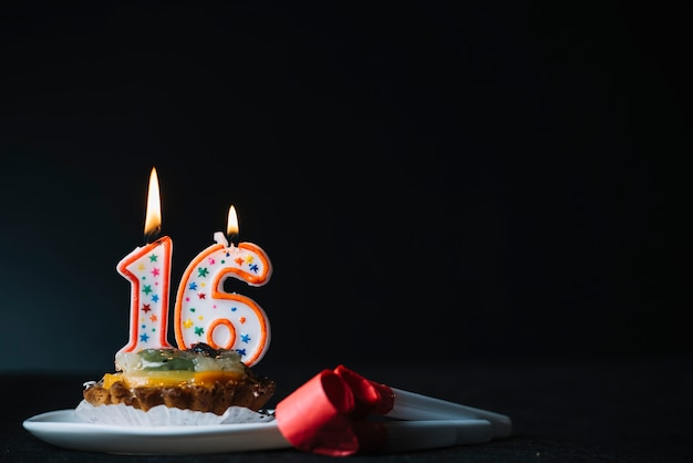 Number 16 birthday lighted candle on the slice of tart and party horn blower against black background Free Photo