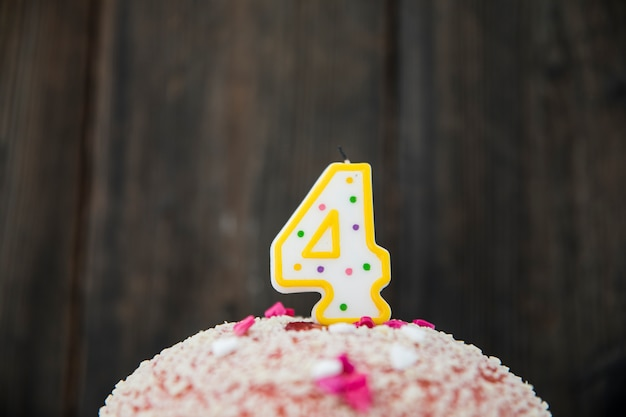 Number 4 Candle In A Birthday Cake Against Blue Wooden Background Free Photo