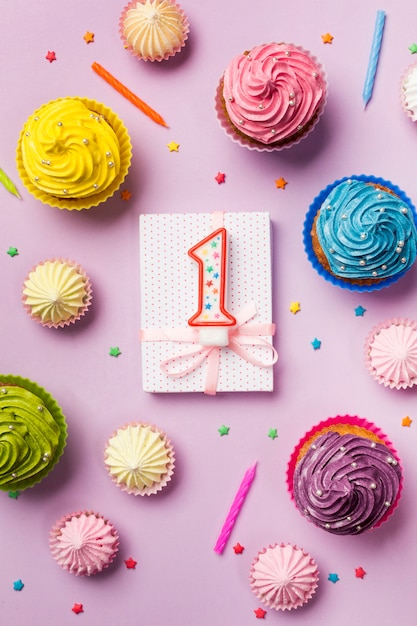 Number one candle on wrapped gift box with decorative muffins; aalaw and sprinkles on pink backdrop Free Photo