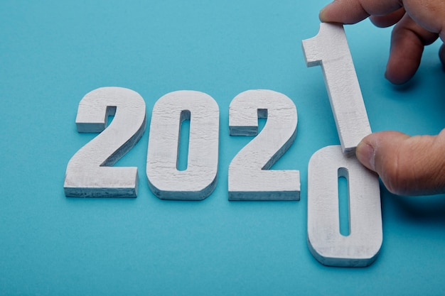 Numbers 2021 and hand on pastel blue background for new year Premium Photo