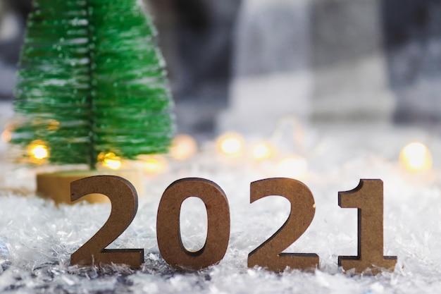 クリスマスツリーとお祝いのぼやけた背景に対する数字 Premium写真