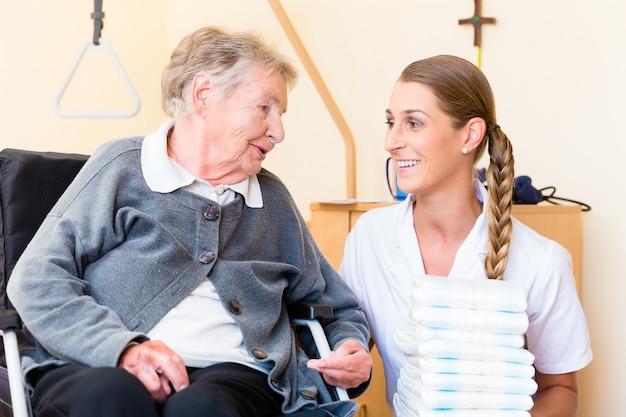 Nurse bringing supplies to woman in retirement home Premium Photo