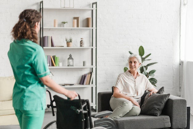 Nurse bringing wheelchair to her senor female patient sitting on couch Free Photo