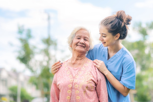 Premium Photo | Nurse caregiver take care of asian elderly woman in the park