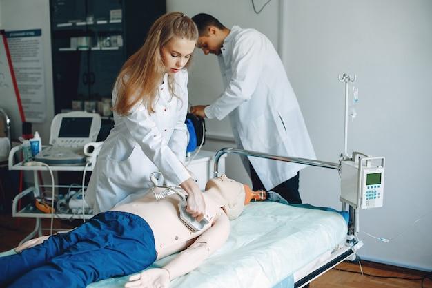 看護師が蘇生を行います。医者は女性が手術を行うのを手伝います。学生は薬を練習します。 無料写真