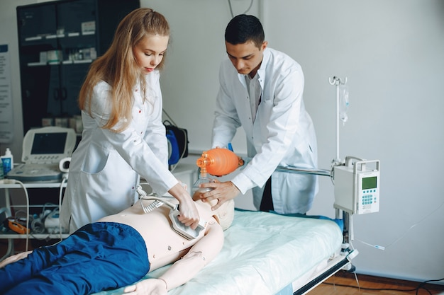看護師が蘇生を行います。医者は女性が手術を行うのを手伝います。 無料写真