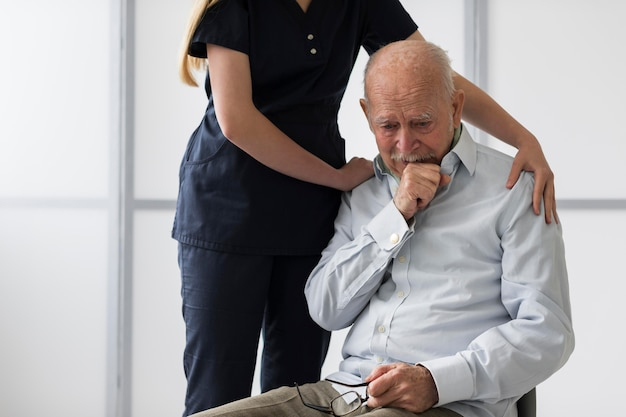 Nurse consoling old crying man Free Photo