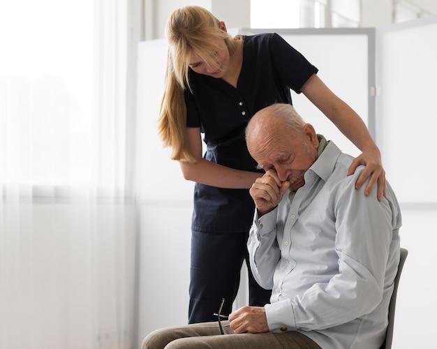 우는 노인을 위로하는 간호사 무료 사진