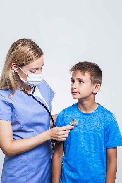 Nurse examining boy with stethoscope Free Photo