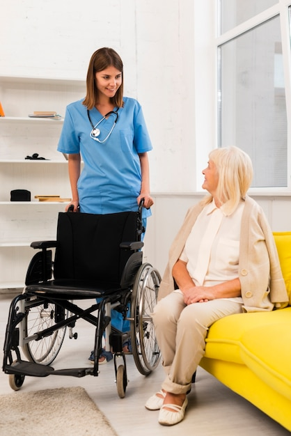 Nurse getting a wheelchair for an old woman Free Photo