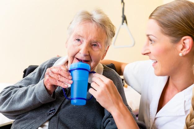 Nurse giving drink to elderly woman in wheelchair Premium Photo