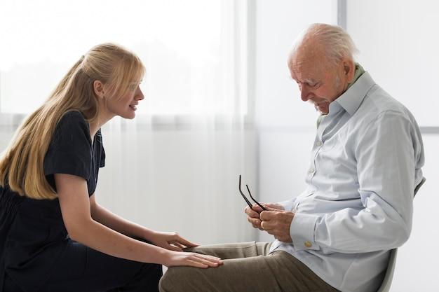요양원에서 노인과 대화를 나누는 간호사 무료 사진