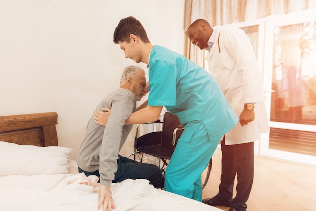 The nurse helps the elderly man to get out of bed. Premium Photo