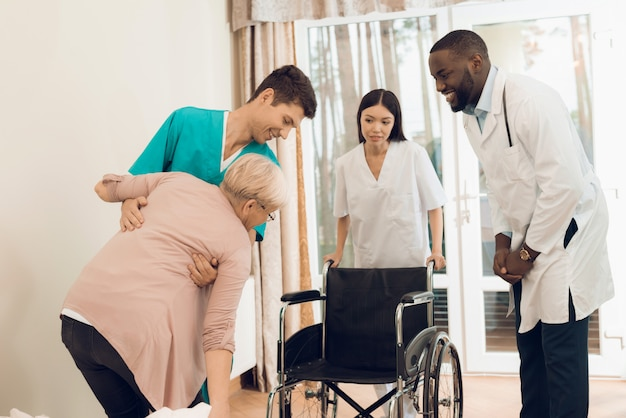 The nurse helps an elderly woman to get into a wheelchair Premium Photo