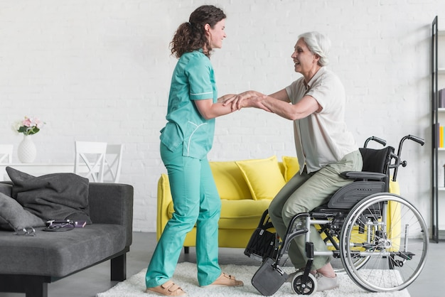 Nurse holding disabled senior woman's hand sitting on wheel chair Free Photo