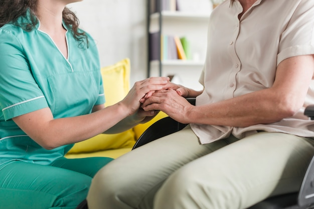 Nurse holding hands of disabled senior woman sitting on wheel chair Free Photo