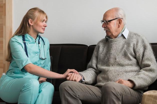Infermiera che tiene la mano dell'uomo anziano in una casa di cura Foto Gratuite