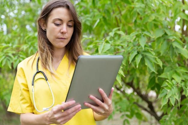手に持ったタブレットをじっと見つめる制服姿の看護師 Premium写真