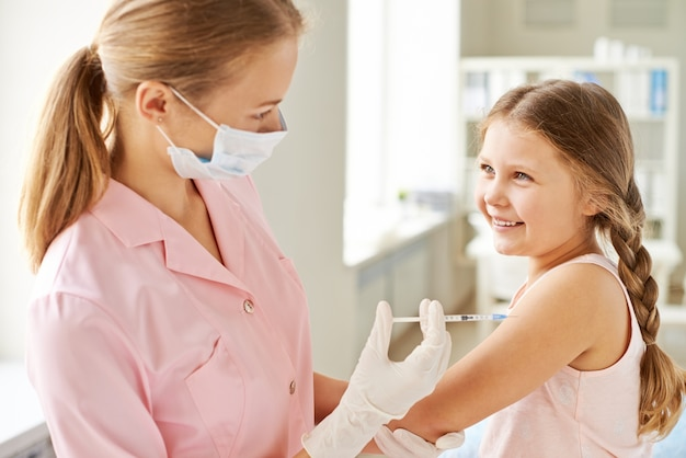 Nurse injecting a smiling girl Free Photo