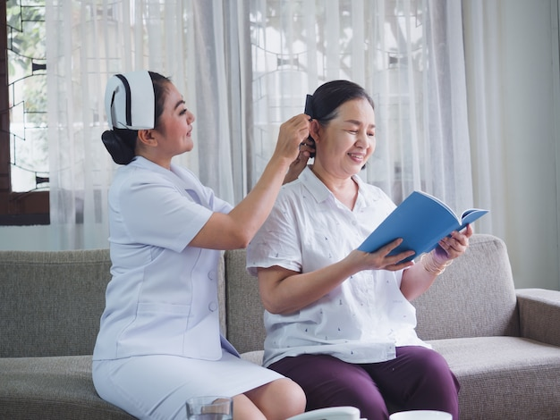 The nurse is combing the hair for the elderly with happiness, old woman read book Premium Photo