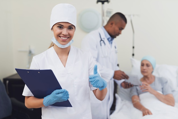 A nurse is posing against the patient's background. Premium Photo