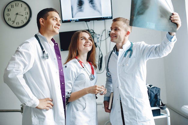 Nurse listens to the doctor.students in hospital gowns. men and woman standing in a hospital ward. Free Photo