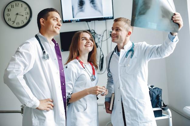 看護師は医者の話を聞きます。病院のガウンを着た学生。病棟に立っている男女。 無料写真