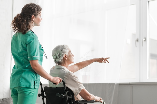 Nurse looking at senior woman sitting in wheelchair pointing toward window Free Photo