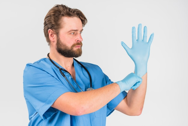 Nurse male with serious face pulling on gloves Free Photo