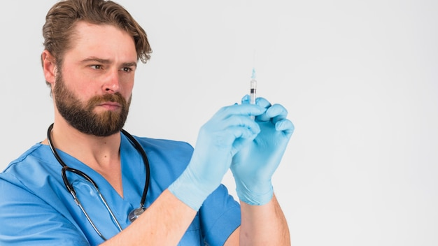 Nurse man in uniform and gloves holding injection Free Photo