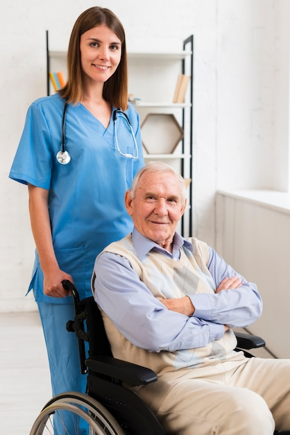 Nurse and old man posing for the camera Free Photo