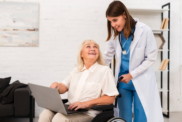 Nurse and old woman checking a laptop Free Photo