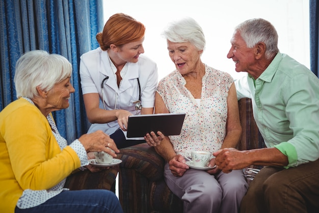 Nurse pointing and showing the screen of a digital tablet to retired person Premium Photo
