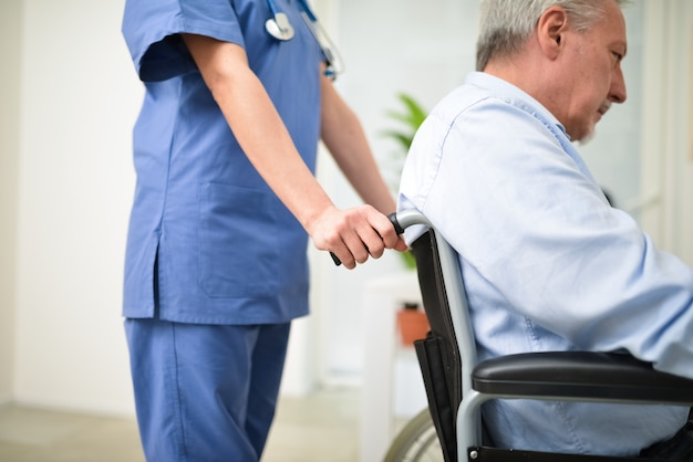 Nurse pushing a patient on a wheelchair Premium Photo